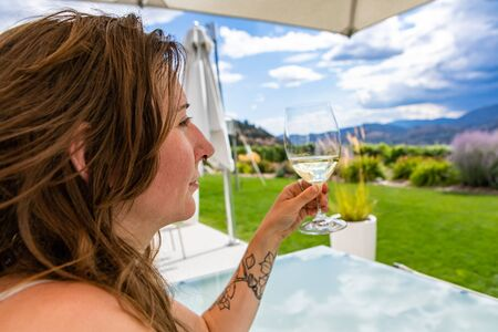 caucasian woman under patio umbrella relaxing, holding and enjoying glass of white wine as she looking to the beautiful landscapes of Okanagan Valley