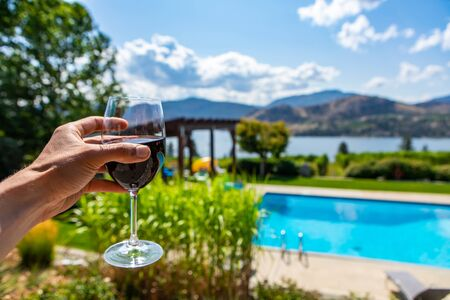 man hand holding glass of red wine selective focus view against blurred background of villa yard with swimming pool on lake and mountains landscape