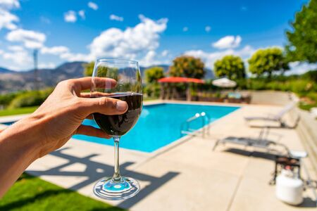 red wine glass on hand selective focus close up against winery restaurant patio with swimming pool background, Okanagan Valley British Columbia Canada