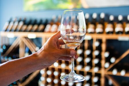 a glass filled with white wine on hand, selective focus close up view against wine bottles on tasting room display wooden shelves racks background