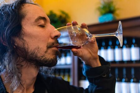 young caucasian man with long hair drinking and tasting red wine with closed eyes, wines bottles display shelves in the background, face side close up