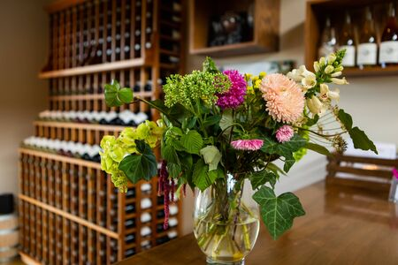 colorful natural flowers on vase selective focus view, winery tasting room wines shop, wine bottles on shelves rack display blurred background