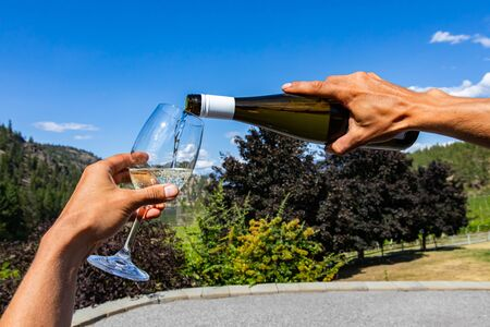 man hands holding white wine bottle pouring wine on the wineglass, selective focus close up against a beautiful landscape, Okanagan Valley, BC, Canada Stock fotó