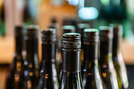 dark amber glass wine bottles neck top close up selective focus view, new bottle black seal screw cap on a winery tasting room display, bottling line