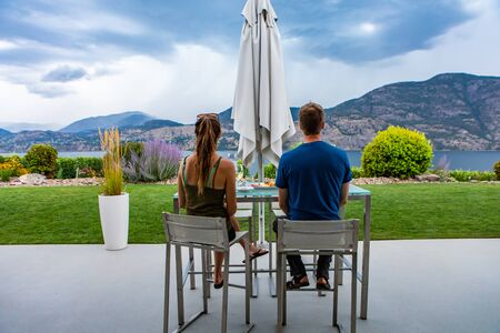 caucasian young man and woman couple back rear view as they tasting wines in restaurant beautiful patio backyard, Okanagan Valley wineries tour visit