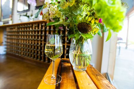 a filled glass of white wine on a wooden table next to a flowers glass vase selective focus, wine bottle racks in the background, tasting room
