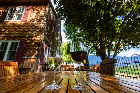 two different glasses sizes and wines, red and white wine on wooden table close up selective focus, farmhouse backyard patio furniture Okanagan Valley Stock fotó