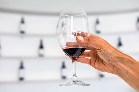 Man hand holding a glass of red wine, selective focus close up view against white tasting room with wine bottles wall rack shelves blurred background Stock fotó