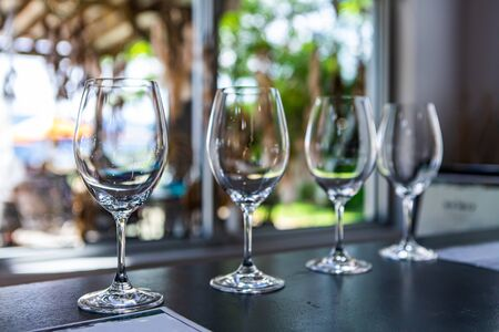 Side by side various sizes of wine empty glasses on a restaurant table selective focus view, goblets for drink and taste wines, tasting room stemware Stock fotó