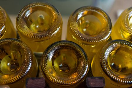 a lot of amber color glass empty wine bottles bottom close up view, with a punt at the base, winery bottling line concept background