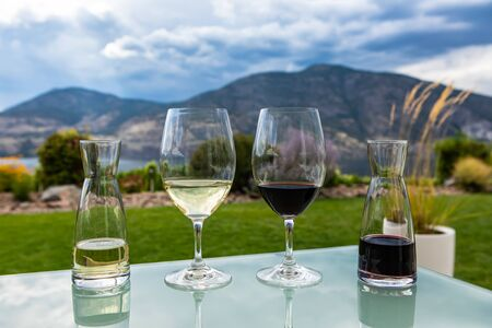 mini decanters and wine glasses filled with red and white wines selective focus, Canadian Okanagan Lake, Valley region, British Columbia BC Canada