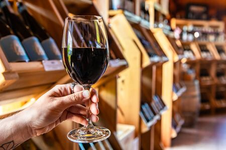 hand holding a glass of red wine selective focus view, tasting room wines bottles display on wooden racks shelves background, wine shop interior Stock fotó