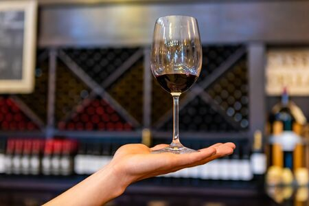 A glass of red wine on hand, selective focus close up view against tasting room bottles storage racks background, blurred copy space on sides Stock fotó