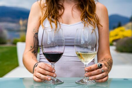 unrecognizable caucasian woman hands with tattoos on pair of red wine and white wine glasses, different wines tasting choosing comparison concept Stock fotó
