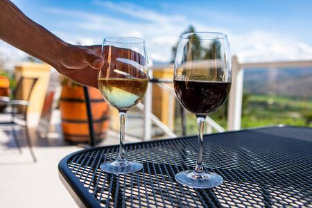 white and red wine glasses on the table, hand choosing and holding white glass, selective focus and close up view, winery wines outdoor testing visit
