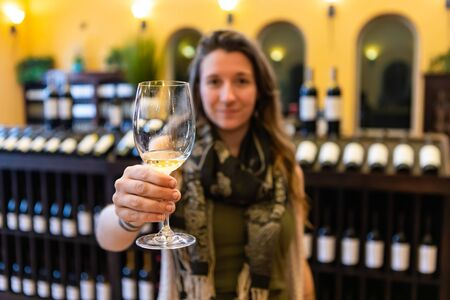 white wine glass selective focus against caucasian young woman hold it and toasting with tasting room wines display shelves blurred background