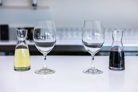 two empty wine glasses and a pair of small decanters filled with white and red wines, taste stemware on a bright white bar counter of the tasting room