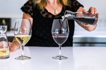 female bartender hand close up as she pouring red wine from a small mini decanter to the wineglass, next to a white glass of wine, bright bar counter Stock fotó
