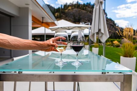 man hand on white wine glass, pair of white and red wines glasses close up selective focus, restaurant patio outdoor table background, Okanagan Valley