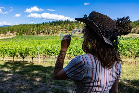 woman wearing hat back view as she drinking and tasting white wine glass, looking to vineyard landscape during hot summer day, Okanagan Valley Canada
