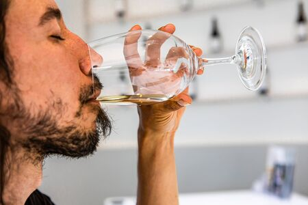 Caucasian man drinking and tasting a glass of white wine with closed eyes, face side selective focus close up view, white interior design copy space Stock fotó