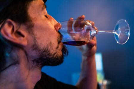 Caucasian man drinking and tasting a glass of red wine with closed eyes, face side selective focus close up view, blurred blue background