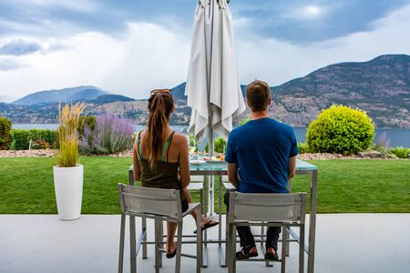 caucasian young man and woman couple back rear view as they tasting wines in the front of beautiful landscape, Okanagan Lake, British Columbia Canada Stock fotó