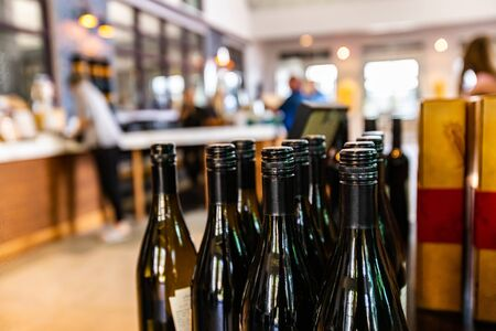 wine bottles, dark amber glass with black screw cap seal closeup selective focus, people buying and tasting wines in the background Stock fotó
