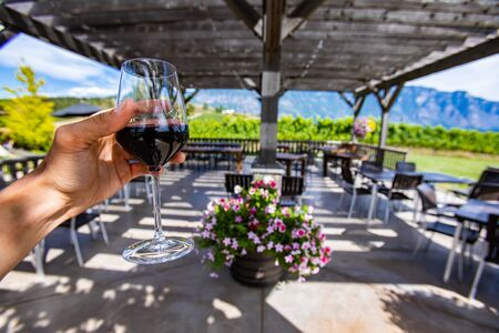 hand holding a glass of red wine selective focus against outdoor wine tasting patio, a winery on Okanagan Valley vineyards, British Columbia, Canada Stock fotó