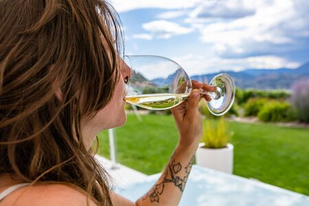 a caucasian woman close up selective focus as she drinking a glass of white wine. outdoor in restaurant tasting patio backyard during winery visit tour