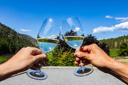 young happy couple hands toasting white wine glasses against beautiful landscape view of Okanagan Valley nature, British Columbia, Canada Stock fotó