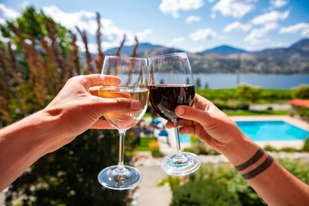 Okanagan Valley wine tasting tour, wineries visit during summer and spring vacations concept, man and woman hands toasting red and white wine glasses