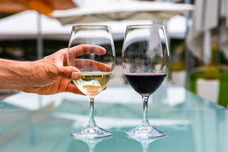 man hand on white wine glass, pair of white and red wines glasses close up selective focus, restaurant patio outdoor table background
