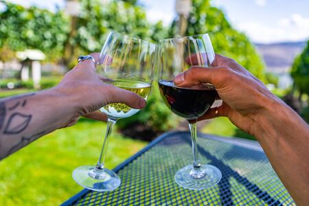 man and woman hands cheering wine glasses as they sitting against beautiful landscape of winery vineyards, happy couple on wines tasting outdoor trip