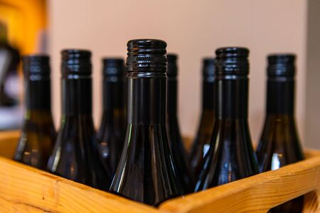 wines bottle dark amber glass top, finish and neck close up, selective focus view of bottles on wooden wine bottle crate, with a black screw cap