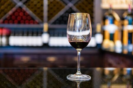 A glass of red wine on black marble countertop selective focus close up view against wine bottles on storage Racks, tasting room blurred background