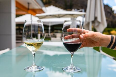 hand on red wine glass, Two glasses of red and white wine, pair of red pinot noir and white chardonnay on a glass table in beautiful patio outdoors