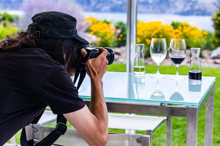man photographer with long hair wearing black rear back view as he takes photos of wine glasses with a professional DSLR camera, wine winery concept