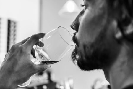 man face side selective focus close up view as he drinking a glass of red wine, alcohol danger concept in black and white Stock fotó