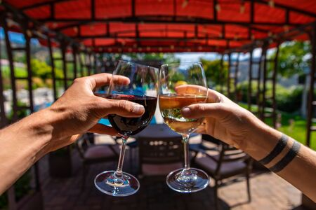 couple hands enjoying and toasting red wine and white wine glasses selective focus, restaurants outdoor seating during sunny summer day background Stock fotó