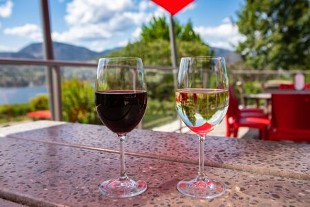 Red wine and white wine glasses selective focus, terrazzo table in restaurant terrace on Okanagan Lake Valley region view, British Columbia BC, Canada