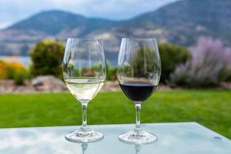 pair of wine glasses filled with red and white wines, selective focus and close up view against yard on Okanagan Lake and mountains background