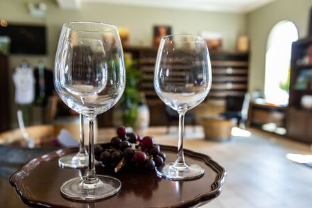 three wine empty glasses on small table with black red grapes selective focus, winery cellar tasting room bottles racks shelves display background
