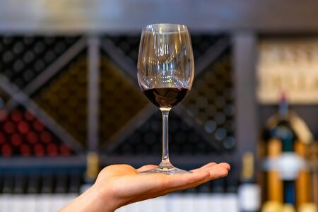 A glass of red wine on hand in selective focus close up view against wine bottles on X cube storage racks, tasting room blurred interior background