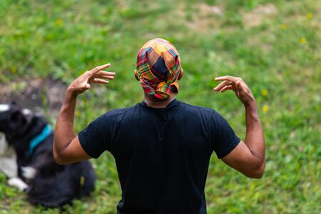 Closeup rear view of male artist wearing colorful handkerchief on head and telling fairytale story during event at world and spoken word festival