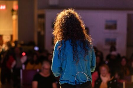 Rear view of curly hair female speaker in blue shirt giving speech in front of defocus audience in auditorium hall during event festival