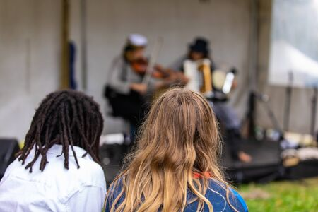 Closeup rear view of woman with dreadlocks hair by female friend looking at artist performing guitar and accordion in event at outdoor