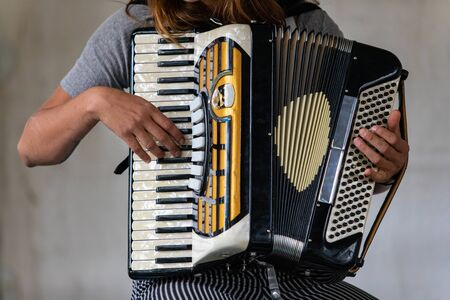 Closeup midsection of female artist wearing gray t-shirt and stripped pant while playing classical accordion and sitting against wall