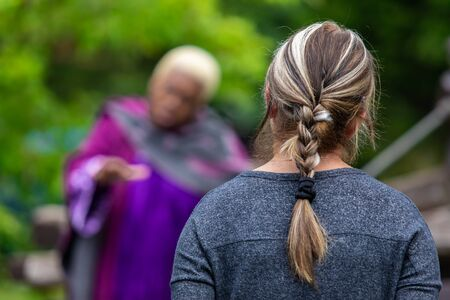 Closeup rear view of woman with tied braided hair while listening fairytale story by female artist during world and word festival against trees