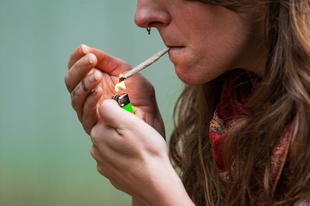 Closeup cropped shot of caucasian womans face with hand rolled marijuana joint held in her lips while her tattooed fingers light the cannabis jay.